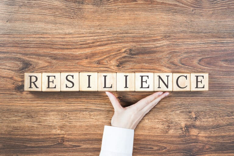 Resilience Word On Wooden Building Blocks With Supporting Hand.